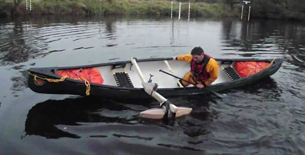 Canoeist demonstrating the extra stability offered by a single outrigger
