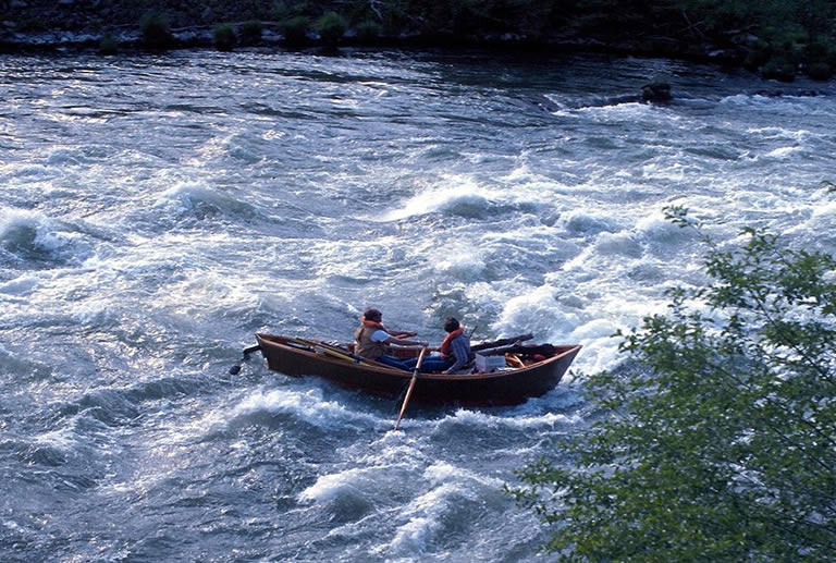 Two people using a drift boat in whitewater